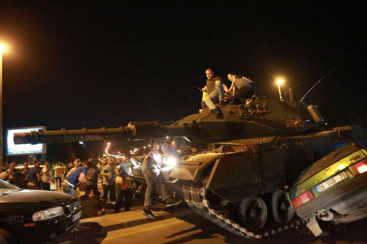 A tank crashes a car as people take streets in Ankara, Turkey during a protest against military coup on July 16.