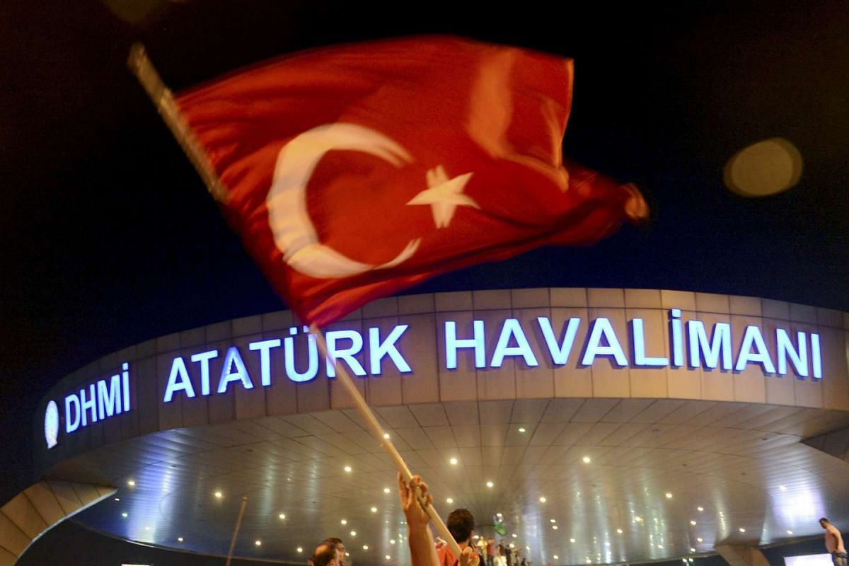 A man waves a Turkish flag in front of Ataturk Airport during an attempted coup in Istanbul, Turkey on July 16.
