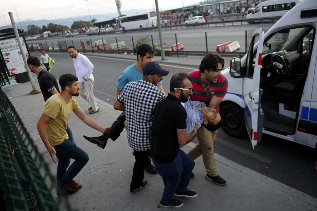 People attend wounded persons near Bosphorus Bridge (background) during an attempted coup in Istanbul, Turkey July 16, 2016.