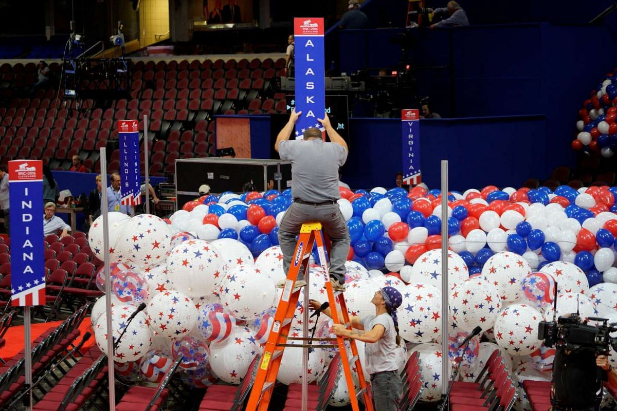 A worker installs the sign for the Alaska delegation on the floor of the Republican National Convention n in Cleveland, Ohio, on July 15, 2016.