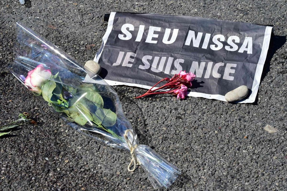 """A rose and a sign reading """"Je suis Nice"""" (I am Nice) placed near a stain on the pavement on la Promenade des Anglais in tribute to the victims of the deadly Bastille Day attack in Nice."""