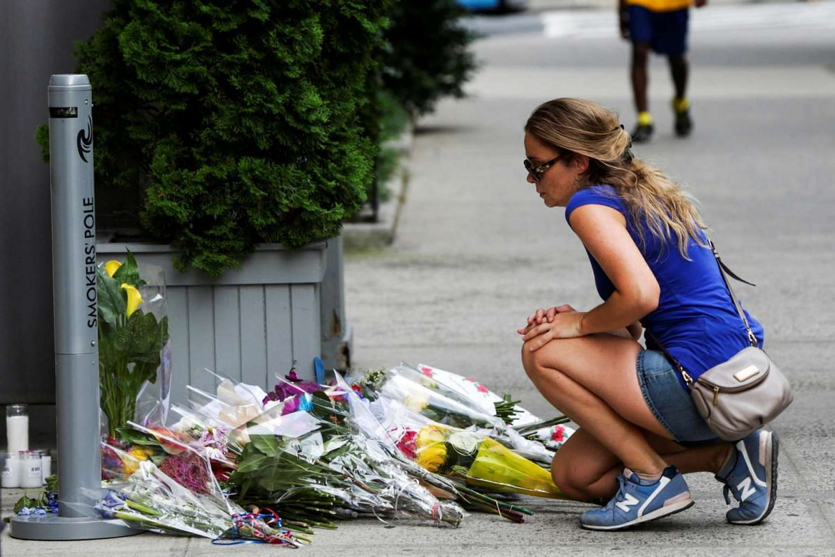 A woman lays flowers on a makeshift memorial at the Consulate General of France in Manhattan following the Nice terror attack on July 16, 2016.