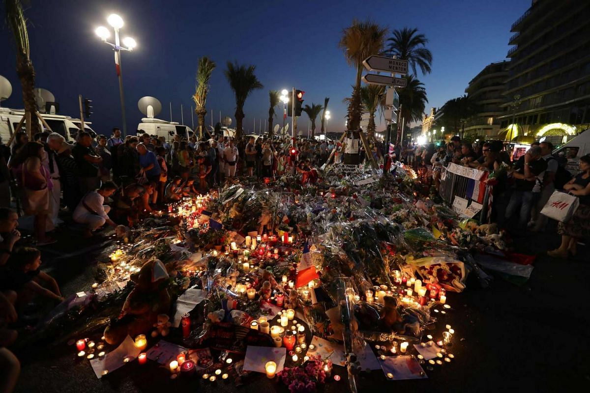 Crowds gather at a make-shift memorial for victims of the deadly Bastille Day attack on the Promenade des Anglais in Nice on July 16, 2016.