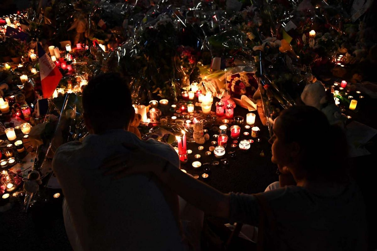People gather at a make-shift memorial placed on the road for victims of the deadly Bastille Day attack on July 17, 2016 in Nice.