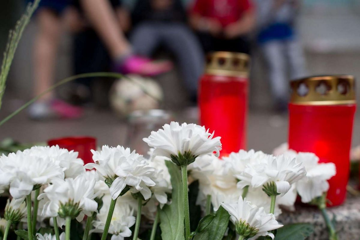Flowers and candles are placed in front of the entrance of Paula Fuerst school in Berlin, Germany on July 17, 2016.
