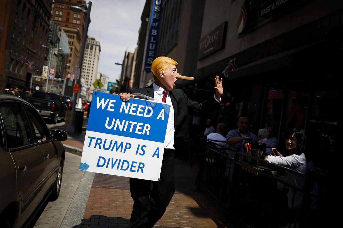 A protester dressed as Donald Trump walks past restaurant patrons ahead of the Republican National Convention in Cleveland, Ohio, US on July 17.