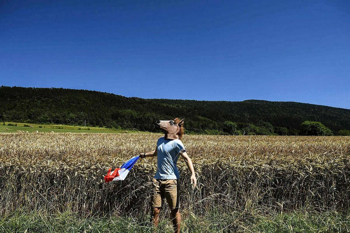 A fan, wearing a fake head of horse, cheers along the road with a French national flag during  the Tour de France cycling race on July 17.