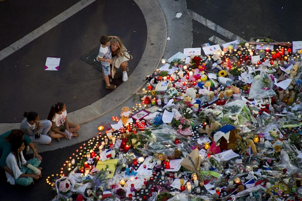 People gather at a makeshift memorial of flowers and candles on the Promenade des Anglais where the truck crashed into the crowd during the Bastille Day celebrations, in Nice, France, on July 17.
