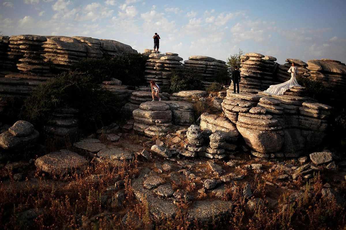 A newly married couple poses for a wedding photographer on the mountainous formations of El Torcal nature park at Antequera Dolmens Site in Antequera, southern Spain, on July 17.