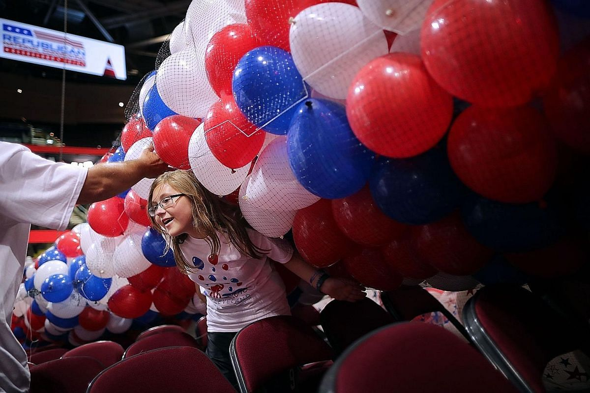 Volunteer June Fertiz, 15, helping to set up nets filled with thousands of red, white and blue balloons before they are lifted into the ceiling of the Quicken Loans Arena where the convention will be held. The convention logo features an elephant - t