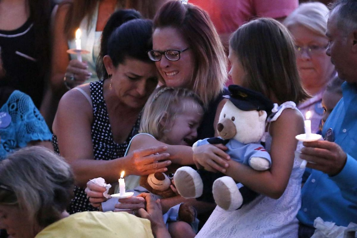 Dechia Gerald, wife of slain officer Matthew Gerald, holds her two daughters at a vigil in Baton Rouge, Louisiana, in the United States on July 18, 2016.