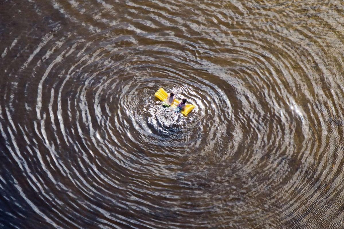 An aerial view shows two children floating in a swimming air mattress in Altwarmbuechener lake in Hannover, Germany, on July 18, 2016.