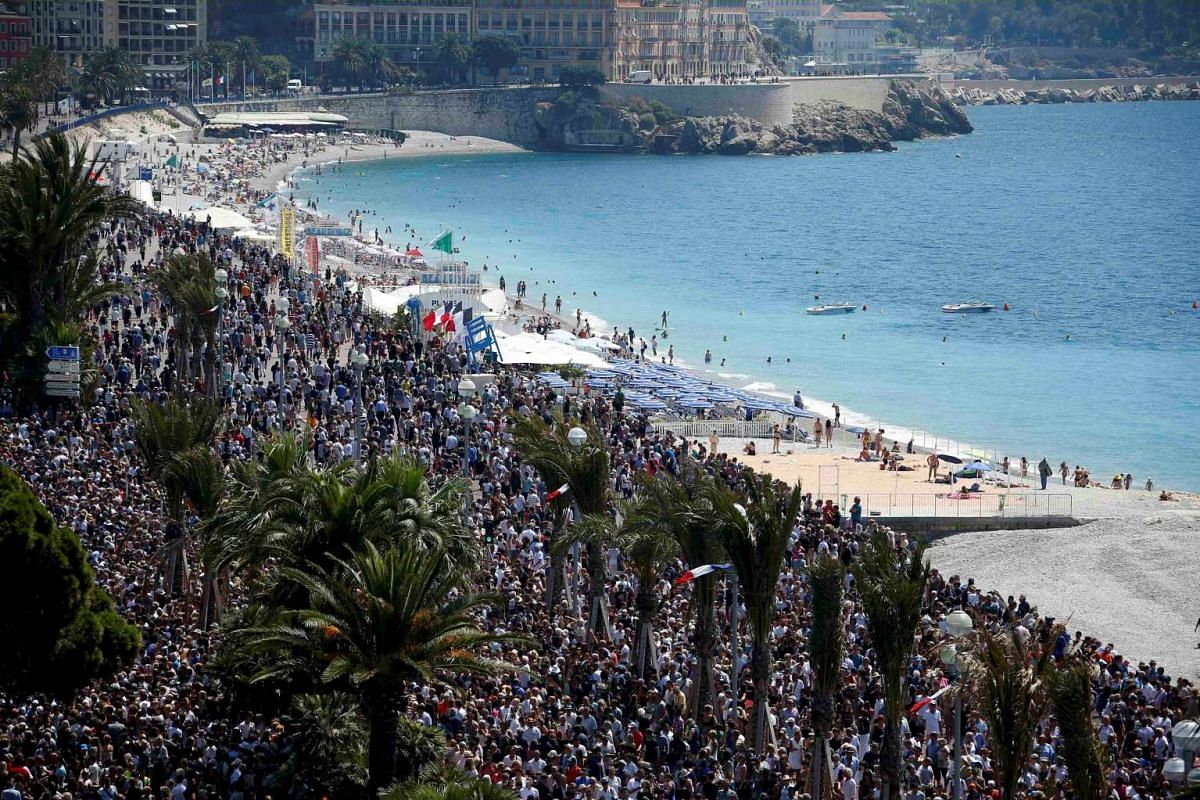 A general view showing the crowd gathering on the Promenade des Anglais during a minute of silence on the third day of national mourning to pay tribute to victims of the truck attack along the Promenade des Anglais on Bastille Day in Nice, France, on