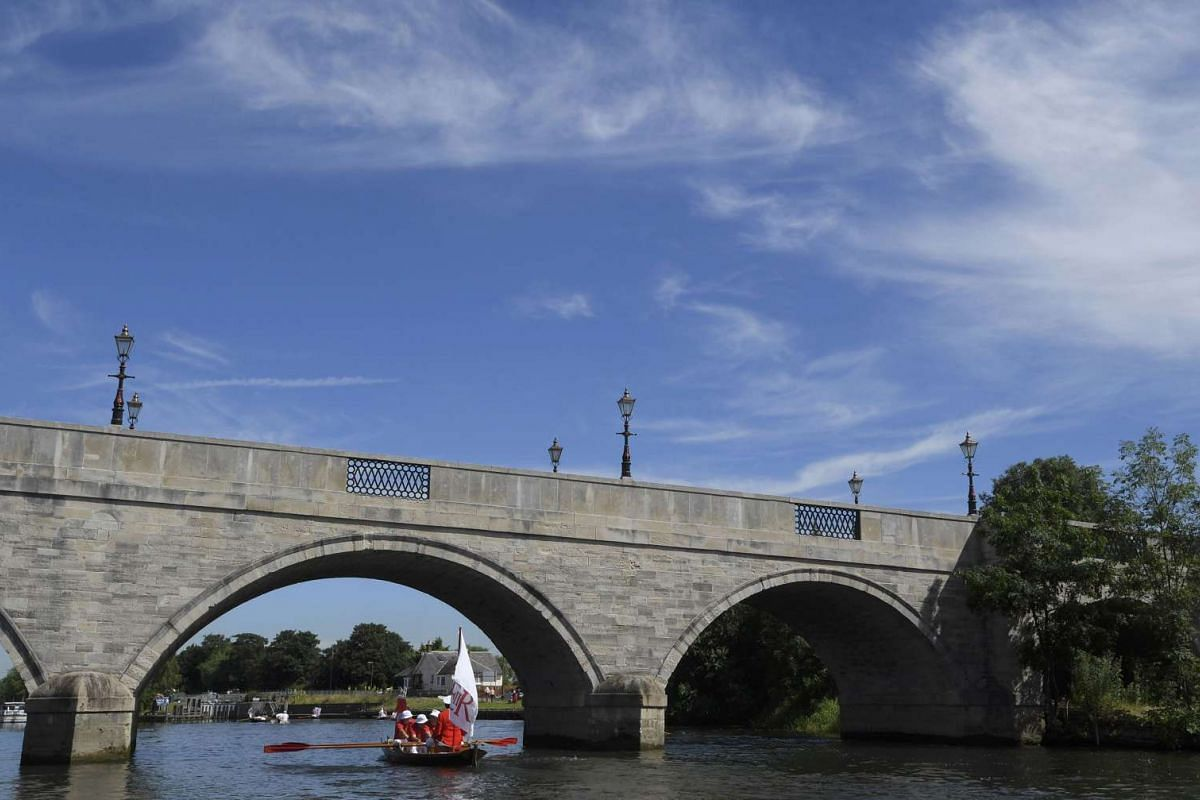 A boat crew rows under Chertsey bridge during Swan Upping, in southern England, on July 18, 2016.