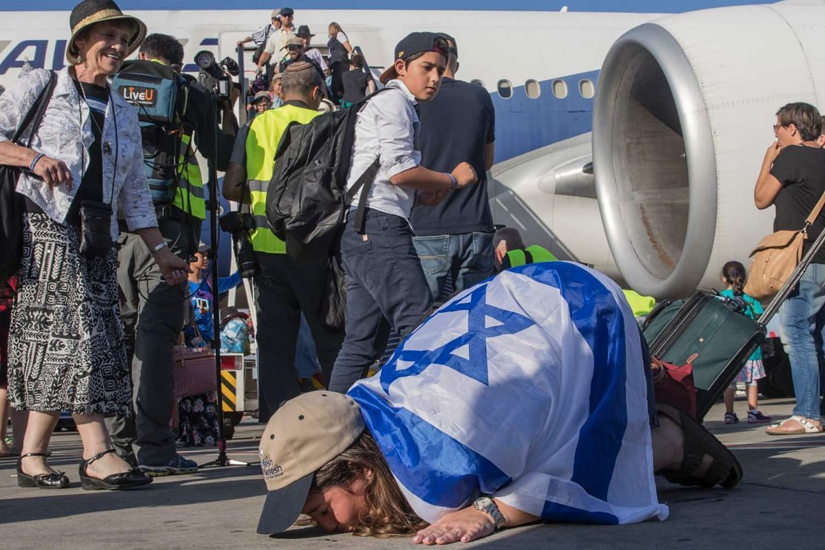 A newly arrived Jewish immigrant coming from North America kisses the tarmac after disembarking a plane upon her arrival at the Ben Gurion International Airport near Tel Aviv on July 19, 2016.