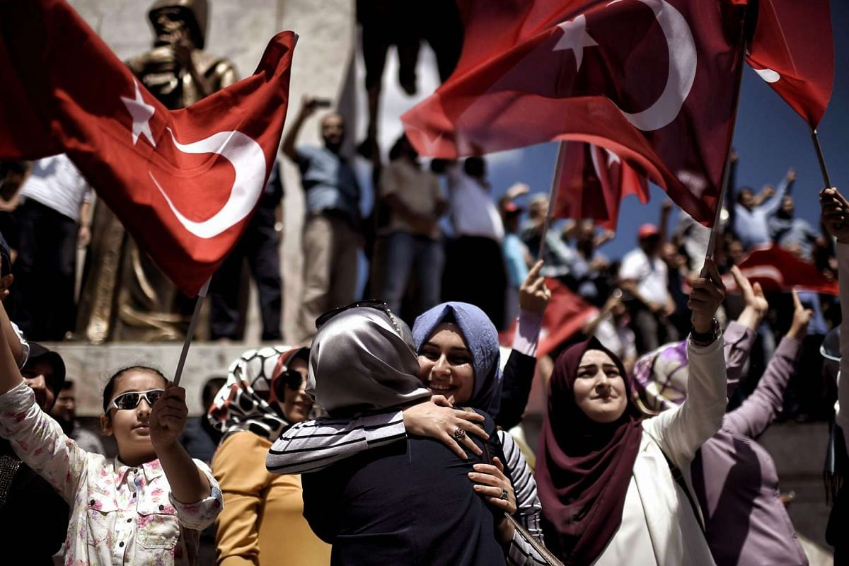 Pro-Erdogan supporters react during a protest at the Sarchane park in Istanbul on July 19, 2016.