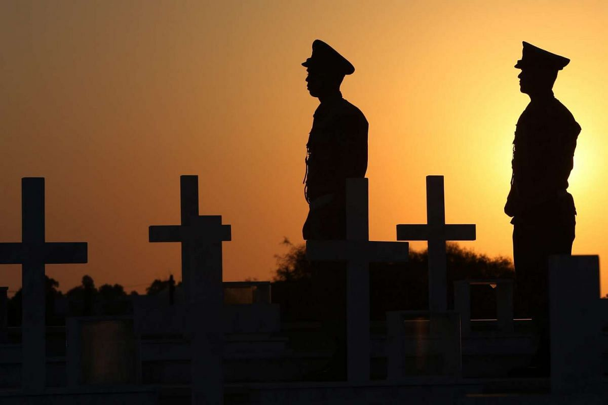 Cypriot soldiers are silhouetted with the crosses marking the graves of Greek and Cypriot soldiers killed in the 1974 Turkish invasion of Cyprus, at the Tymvos Macedonitissas military cemetery in Nicosia, Cyprus on July 19, 2016.