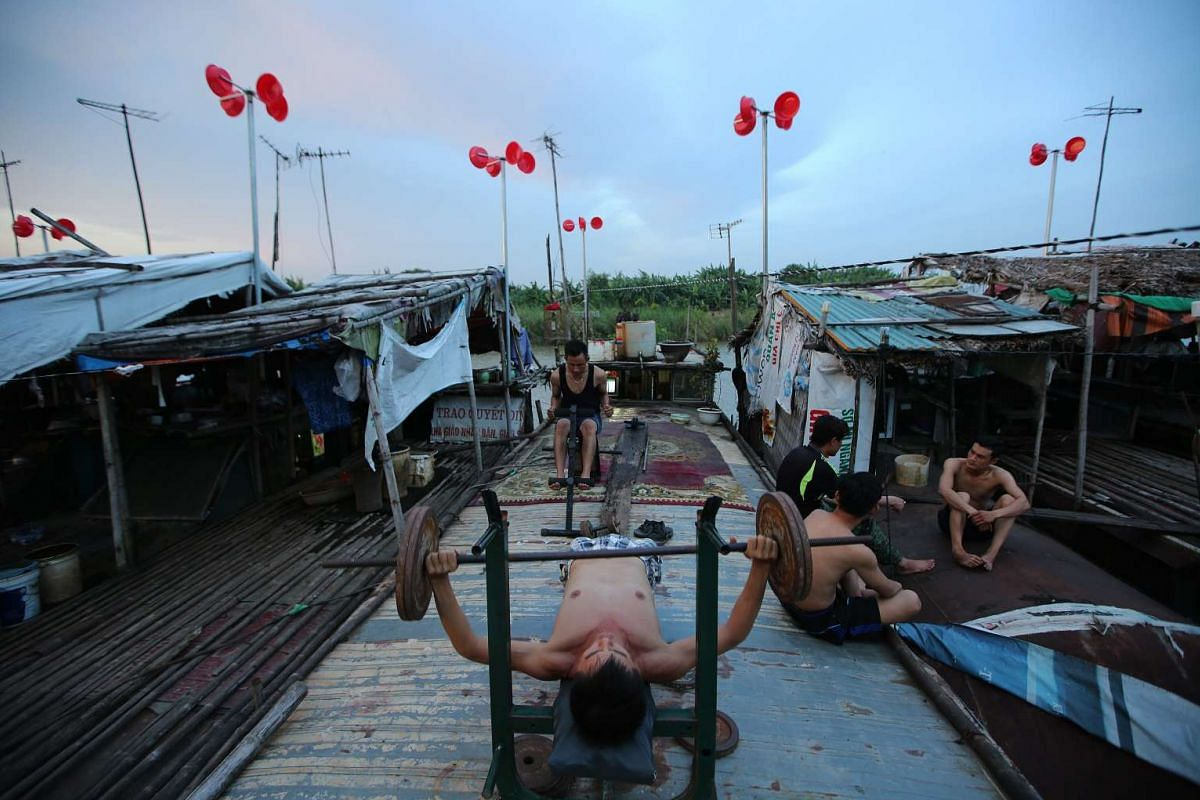 Men exercise next to a wind power system made from plastic buckets at a floating village in Tay Ho District, in Hanoi, Vietnam on July 18, 2016.