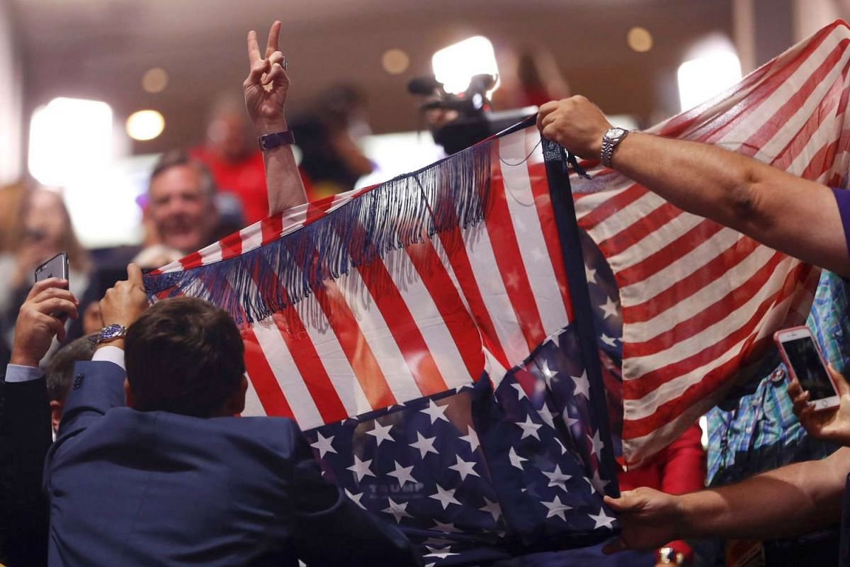 Supporters of Republican US presidential nominee Donald Trump attempt to obscure a protestor from the activist group Code Pink during the second day of the Republican National Convention in Cleveland, Ohio on July 19, 2016.