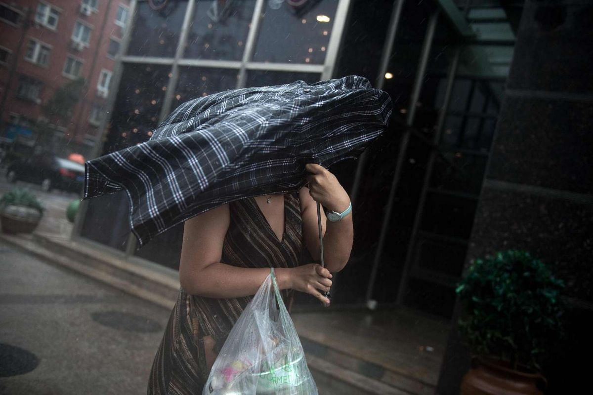 A woman struggles with her umbrella in strong winds and rain in Beijing on July 20, 2016.