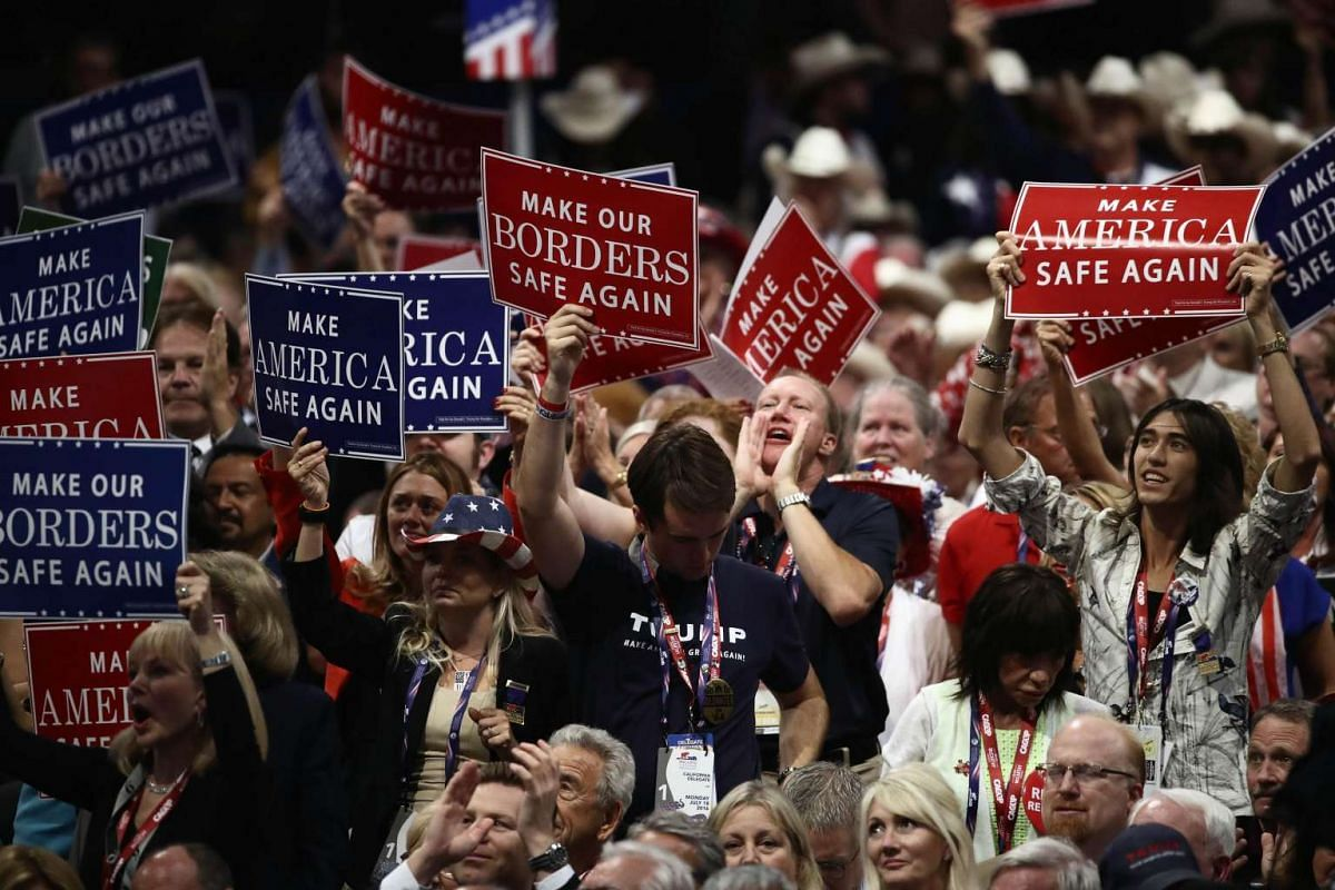 Delegates cheer during a speech while holding signs on the first day of the Republican National Convention on July 18, at the Quicken Loans Arena in Cleveland, Ohio.