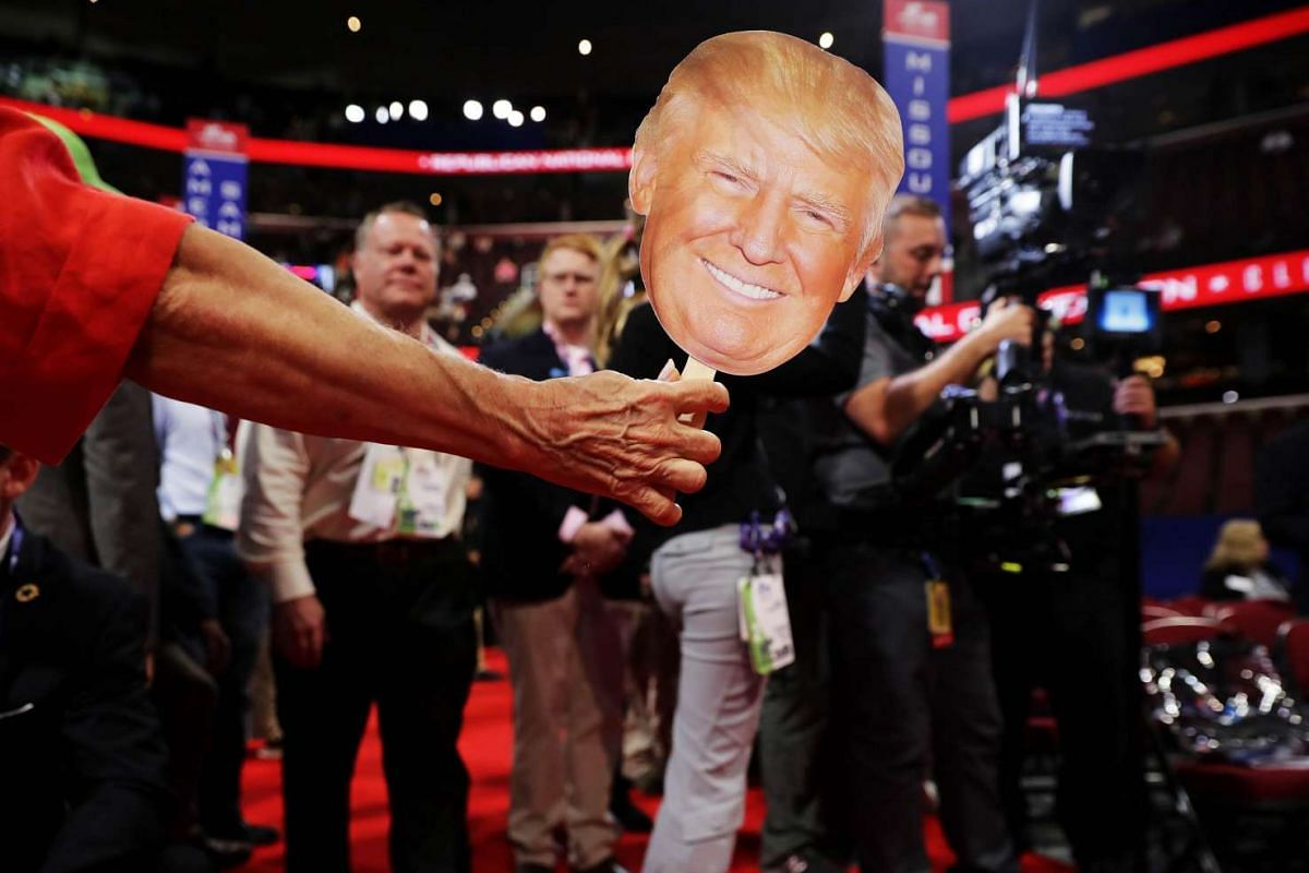 An attendee holds a Donald Trump mask on the floor prior to the start of the second day of the Republican National Convention on July 19, at the Quicken Loans Arena in Cleveland, Ohio.