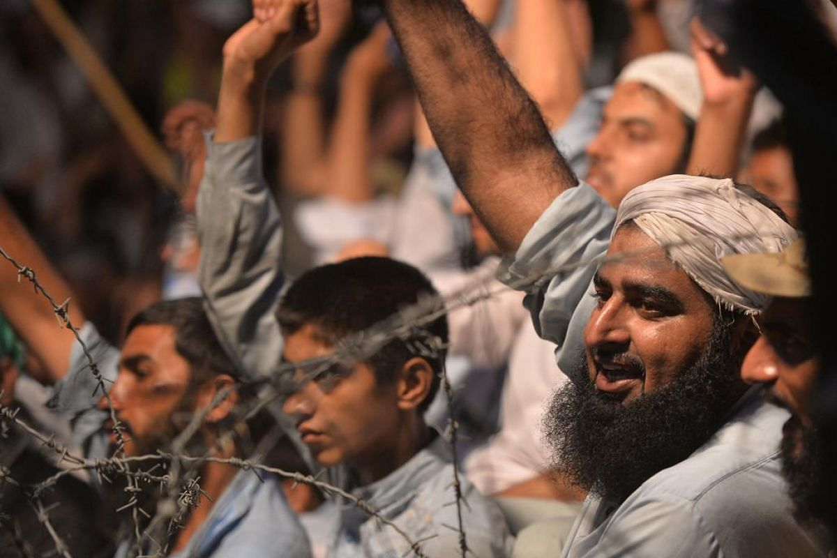 Men raise their fists near barbed wire at a rally as a show of solidarity with Indian Kashmiri Muslims as they observe a Black Day to denounce the actions of Indian security forces in Indian-administered Kashmir, in Islamabad on July 20, 2016.