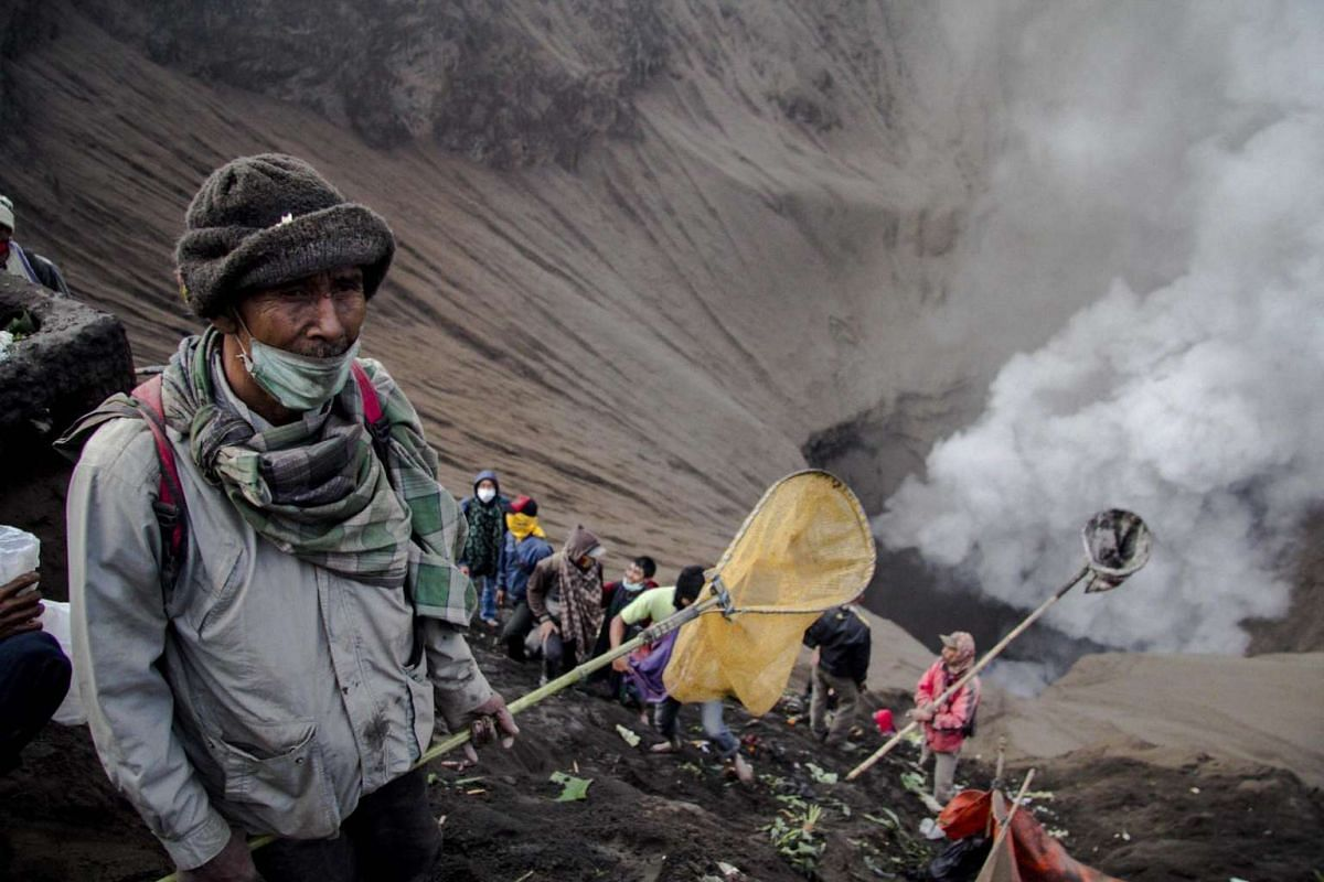 Indonesian villagers use nets and sarongs as they wait for offerings thrown by Hindu worshippers at the crater of Mount Bromo during the Yadnya Kasada Festival in Probolinggo, East Java, Indonesia on July 20, 2016.
