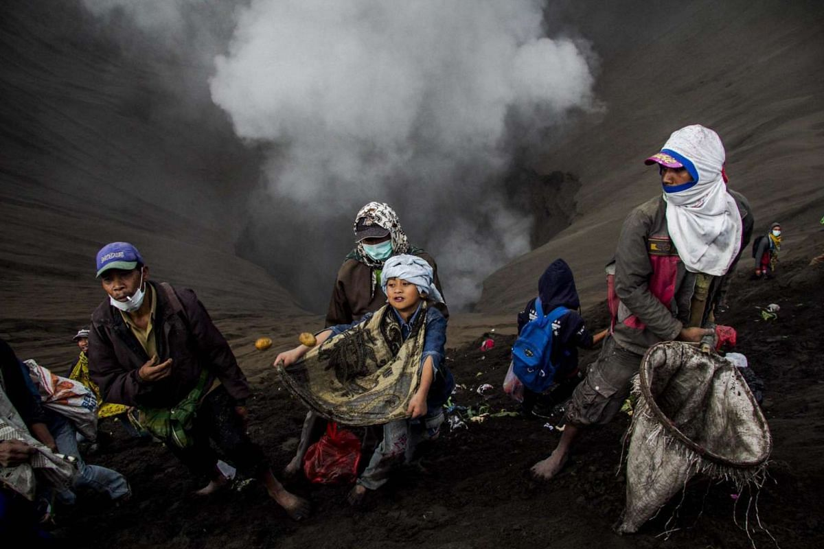 Indonesian villagers use nets and sarong as they wait for offerings to be thrown by Hindu worshippers at the crater of Mount Bromo during the Yadnya Kasada Festival in Probolinggo, East Java, Indonesia on July 20, 2016.