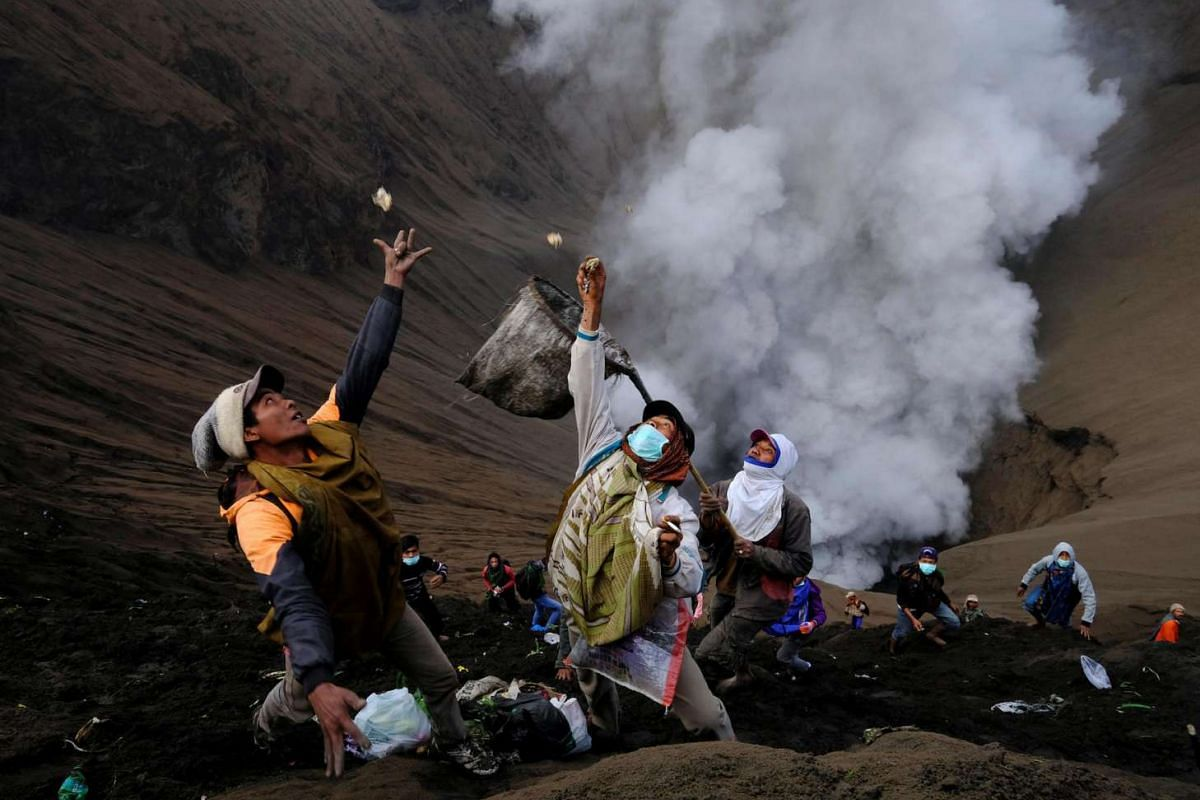 Villagers standing on the slopes near the crater of Mount Bromo try to catch money thrown in by worshippers as smoke and ash rise from the volcano, during the Kasada ceremony in Probolinggo, Indonesia, on July 21, 2016.