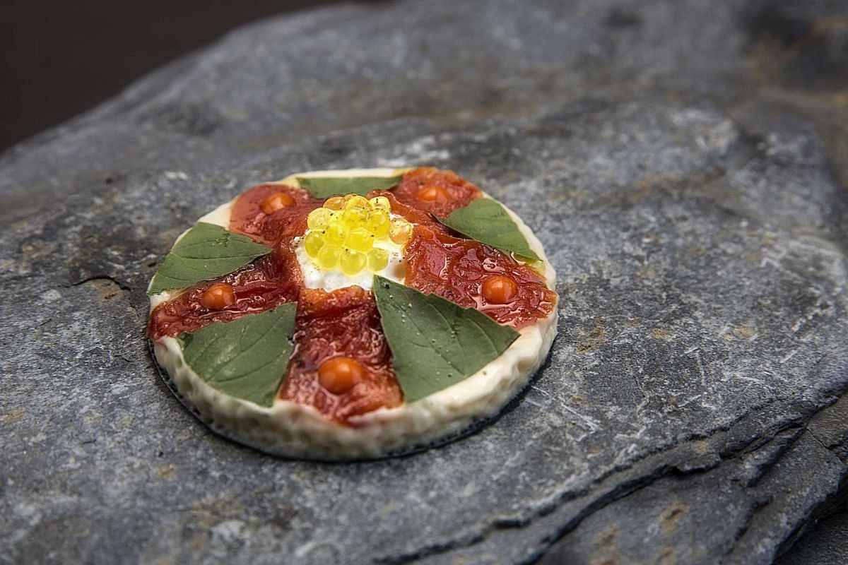 Corner House's chef Jason Tan creates a special pizza using burrata and basil and topped with olive oil spheres.
