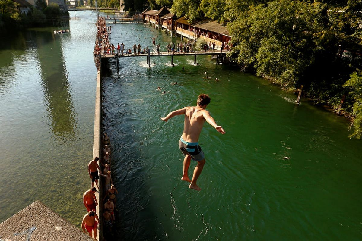 A man jumps from a bridge into the Limmat river as temperatures swell in Zurich, Switzerland on July 20.
