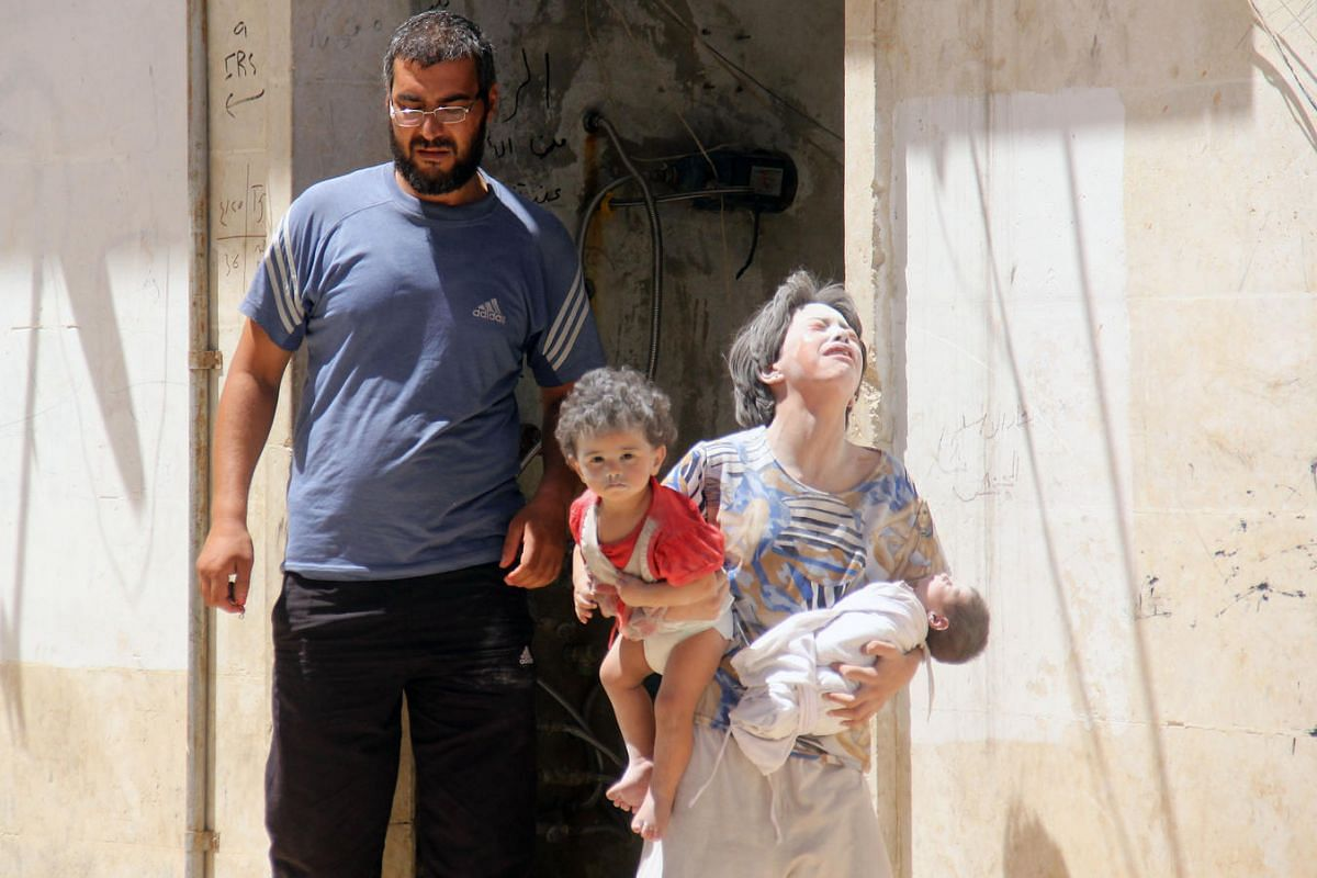 Syrian civilians are seen following a reported air strike by the government on the rebel-held northwestern city of Idlib, on July 20. More than 280,000 people have been killed and millions displaced since Syria's civil war erupted in 2011.