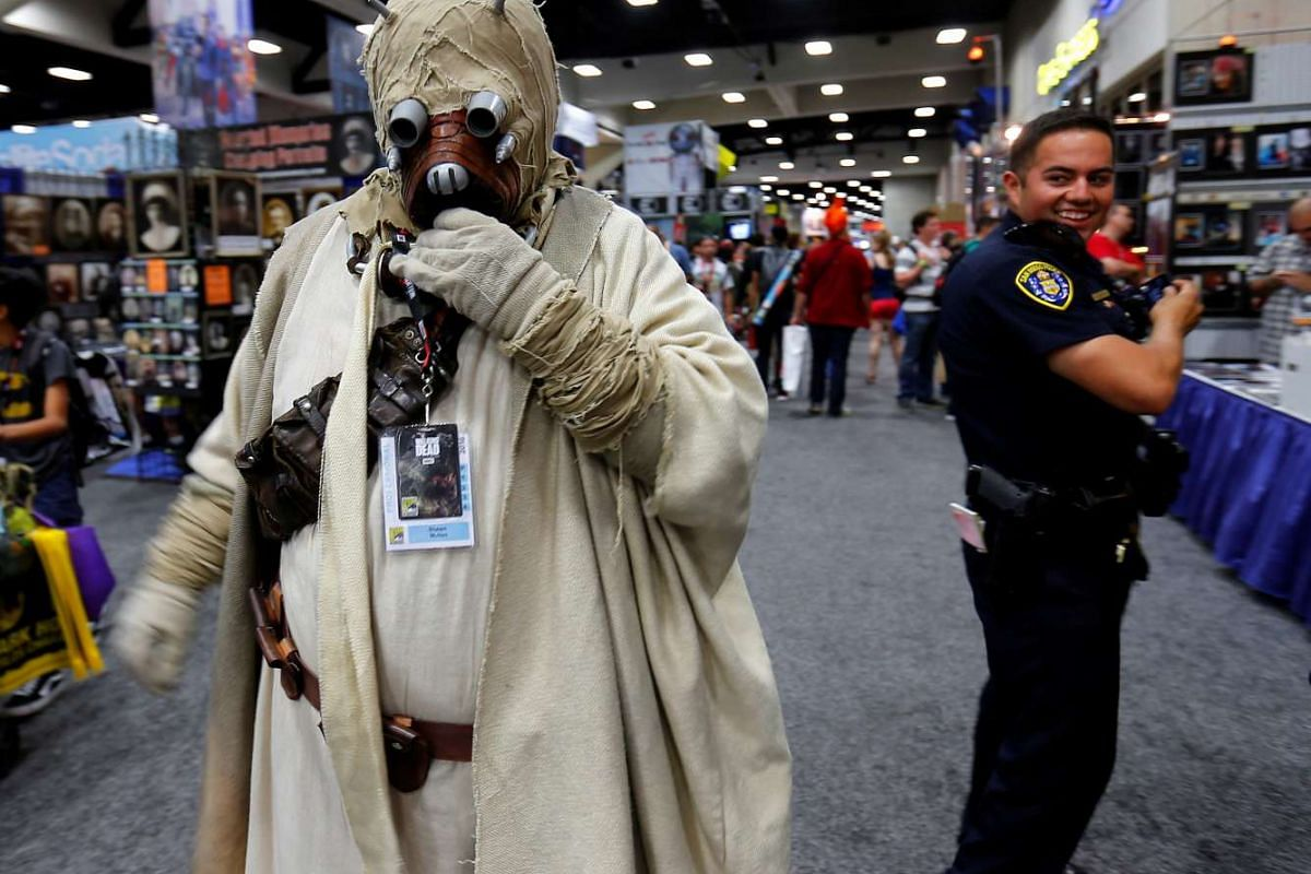 A San Diego police officer takes a second look at an attendee's Star Wars Tusken Raider costume while patrolling the convention floor during opening day of Comic-Con International in San Diego.