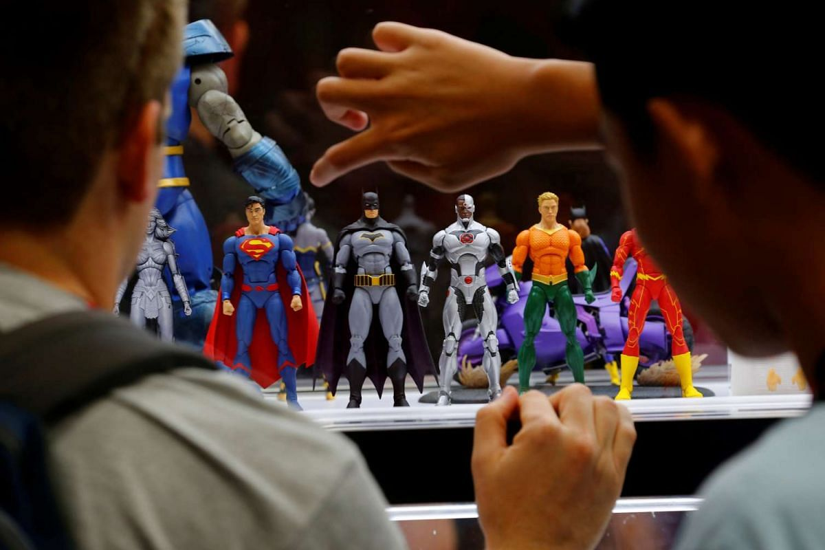 Attendees look over a display of mini DC Comics superhero replicas - Superman, Batman, Cyborg, Aquaman and The Flash - during opening day of Comic-Con International in San Diego, California, United States on July 21.