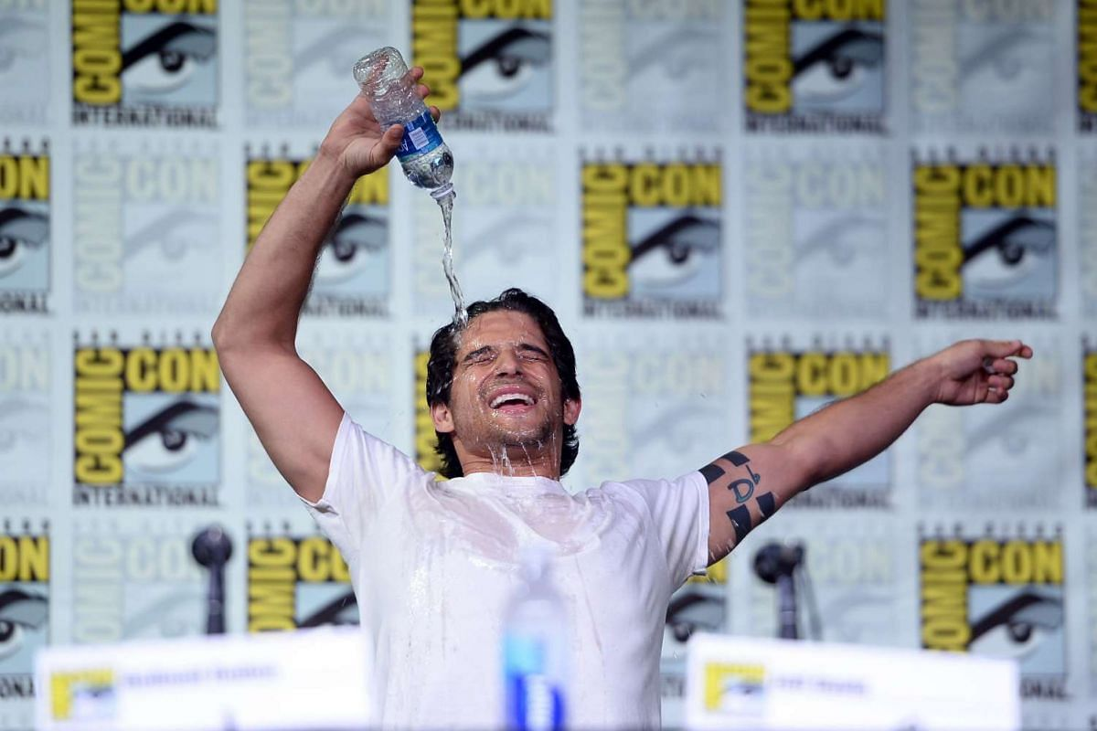 """Actor Tyler Posey pours a bottle of water on himself during the """"Teen Wolf"""" panel during Comic-Con International 2016 at San Diego Convention Center on July 21."""