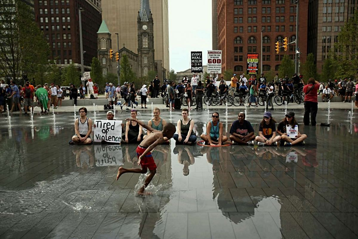 Demonstrators sit together in a fountain inside the Event Zone of the 2016 Republican National Convention in Cleveland, Ohio on July 21, 2016.