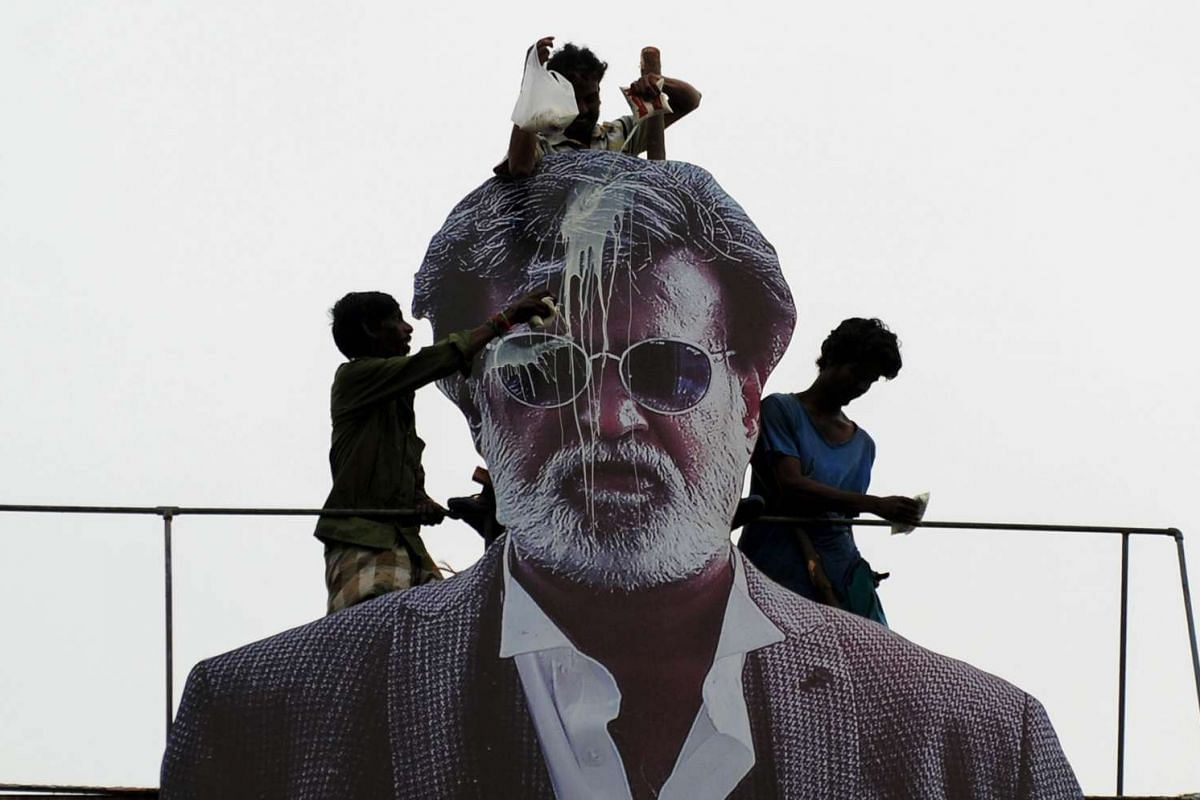 Indian fans pour milk to bless a cut-out image of Bollywood star Rajinikanth outside a cinema on the first day of release of his new Tamil-language film Kabali in Chennai on July 22, 2016.
