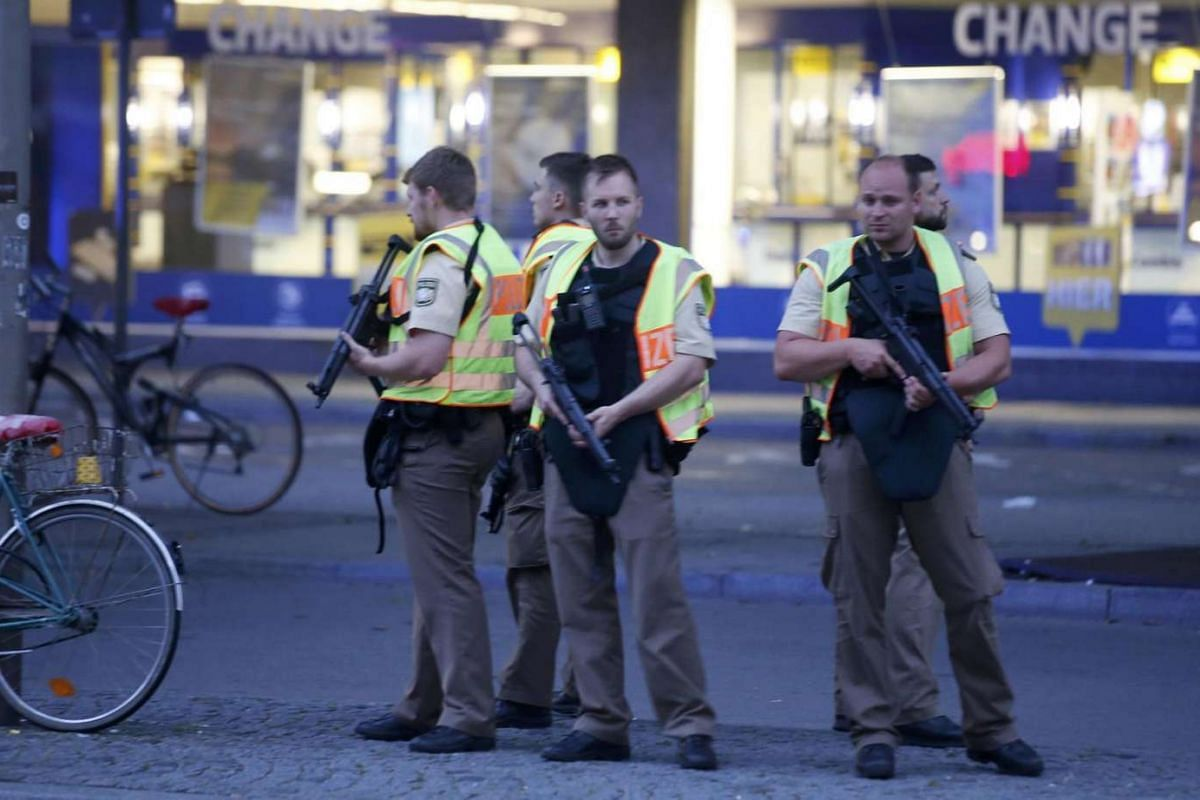 Police officers stand guard outside the main train station following a shooting rampage at the Olympia shopping mall in Munich, Germany on July 22.