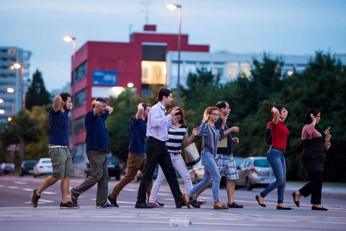 Evacuated people from the shopping mall walk with their hands up in Munich on July 22 following a shooting earlier.