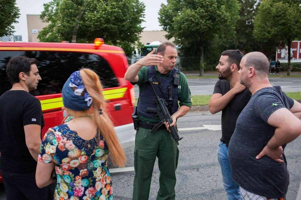 A policeman explains the situation to people, near a shopping mall (the Olympia Einkaufzentrum (OEZ) ) in Munich on July 22 following shootings.
