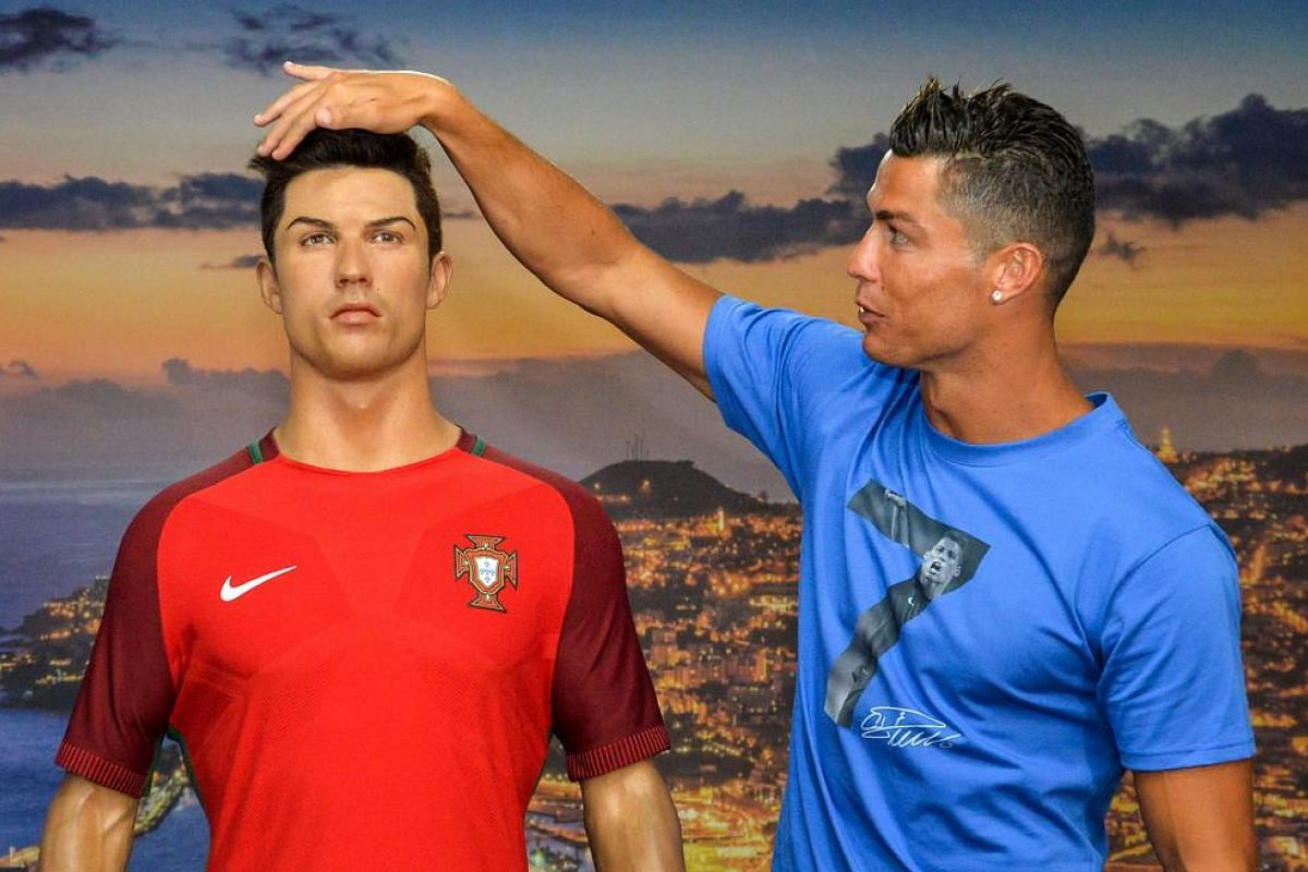 Portugese forward Cristiano Ronaldo poses next to a wax statue representing himself during a visit to the new location of the CR7 museum dedicated his professional career at Funchal, on the Portuguese island of Madeira on July 23.