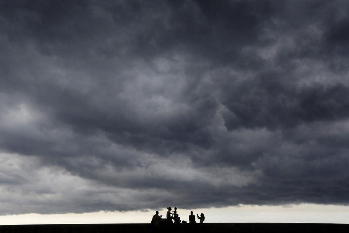 Storm clouds are seen in the sky as people sit on Havana's seafront boulevard El Malecon, Cuba, July 23.