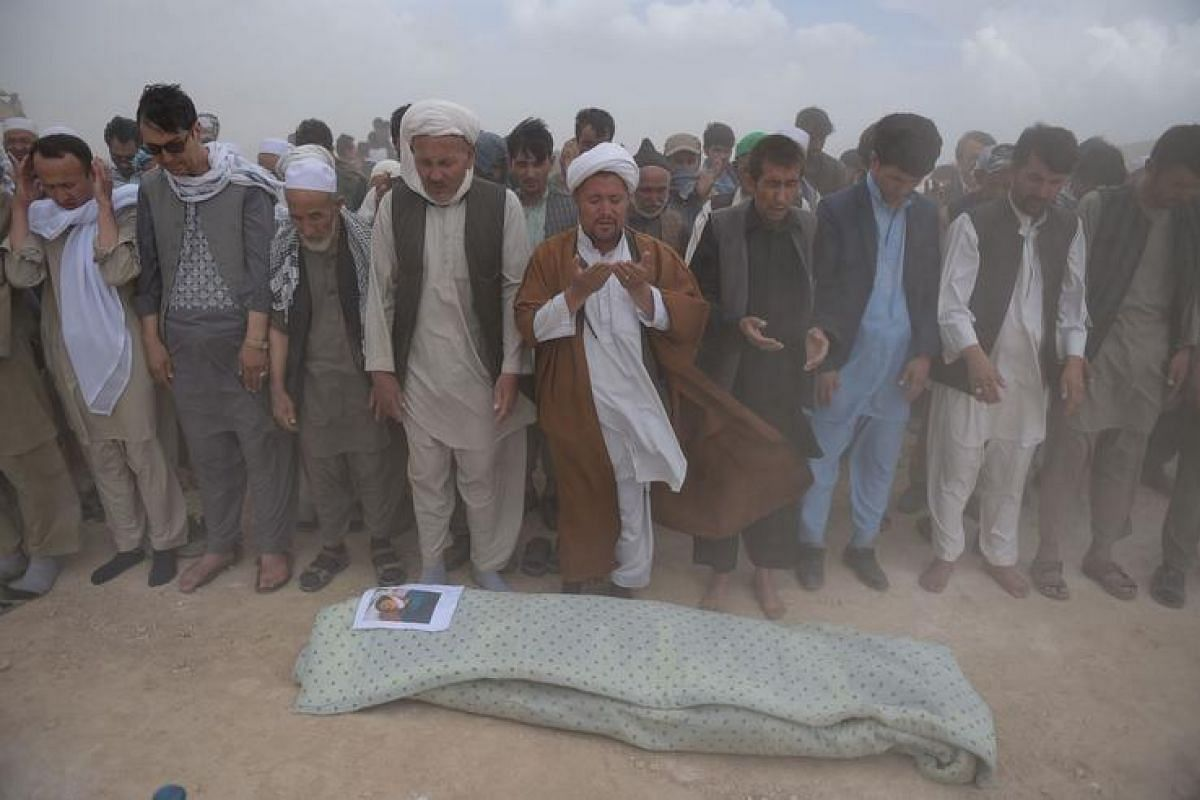 Afghan mourners offer funeral prayers for one of the 80 victims killed in a twin suicide attack, in Kabul on July 24.