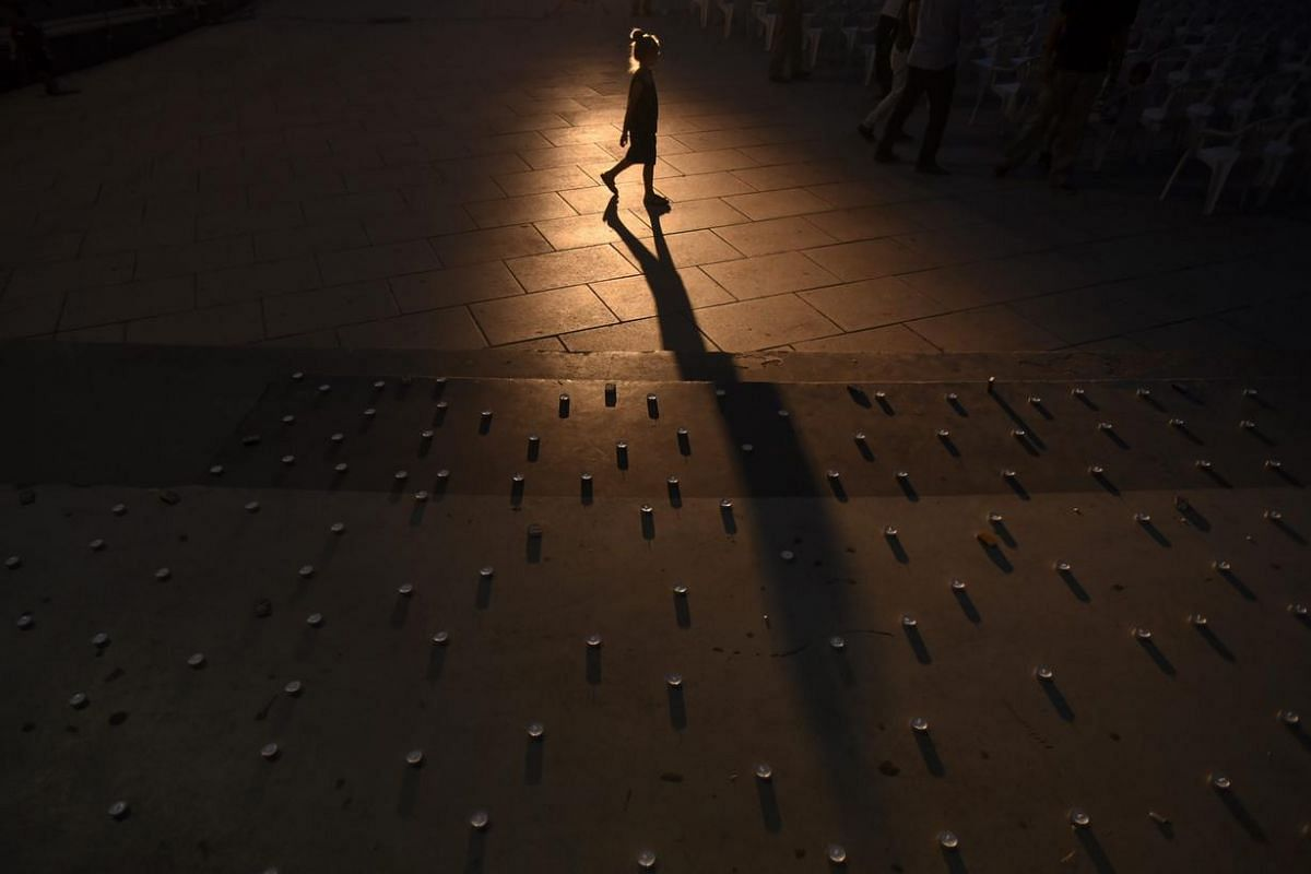 A Kosovo Albanian girl walks past candles in the city square as they pay respect to the victims of the shooting spree in Munich, in Pristina, Kosovo July 24.  According to authorities, at least 10 people died, three of them being Albanians, including