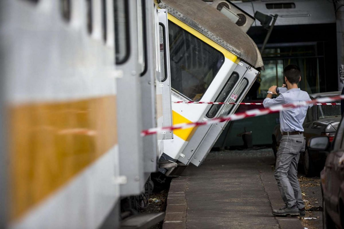 A man takes a photo at the scene of a crash between a tram and a train in Porta Maggiore Square, in Rome, Italy, July 25, 2016. Five passengers were slightly injured in the crash. PHOTO: EPA