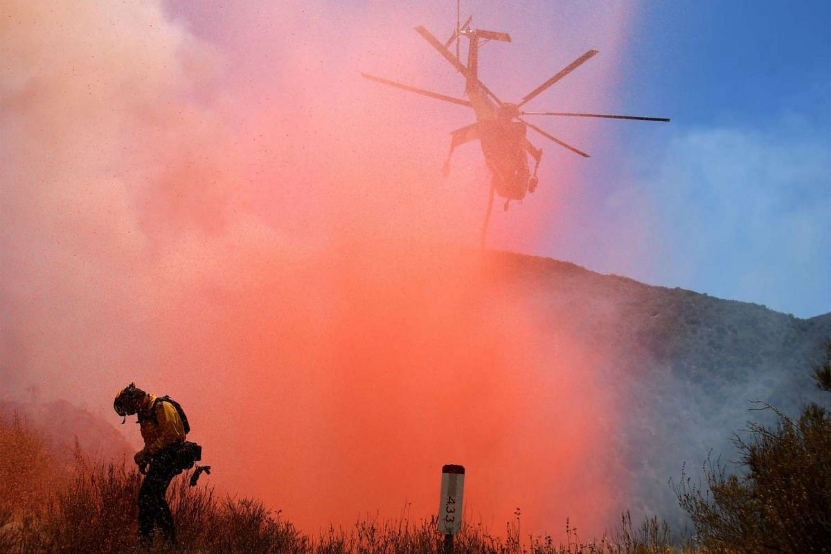 A fire fighter is sprayed with retardant as a helicopter makes a drop as emergency workers continue to battle the so-called Sand Fire in the Angeles National Forest near Los Angeles, California, United States, July 25, 2016. PHOTO: REUTERS