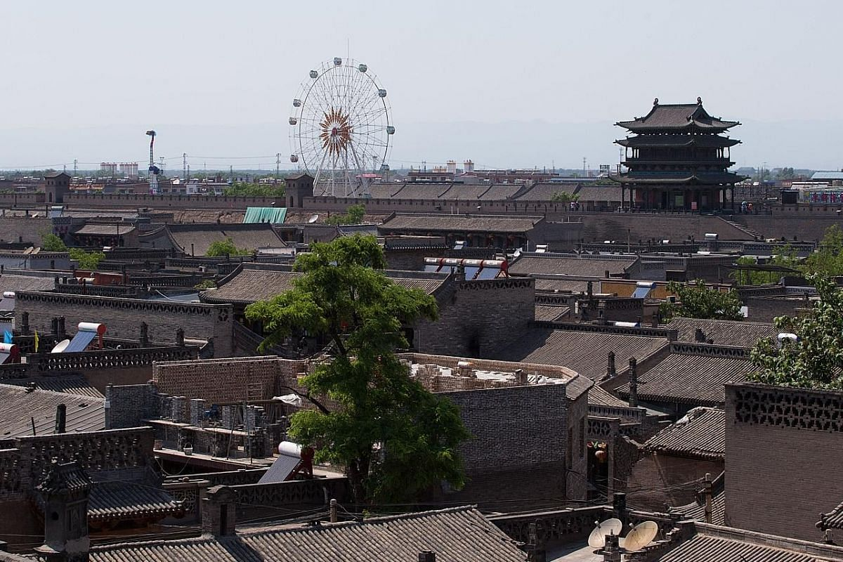 Performers at an event in Zhanjiajie (above) and a ferris wheel in the ancient town of Pingyao (right) show the impact of tourism on China's world heritage sites. Revenue from tourists is needed to recoup the money spent by local governments in apply