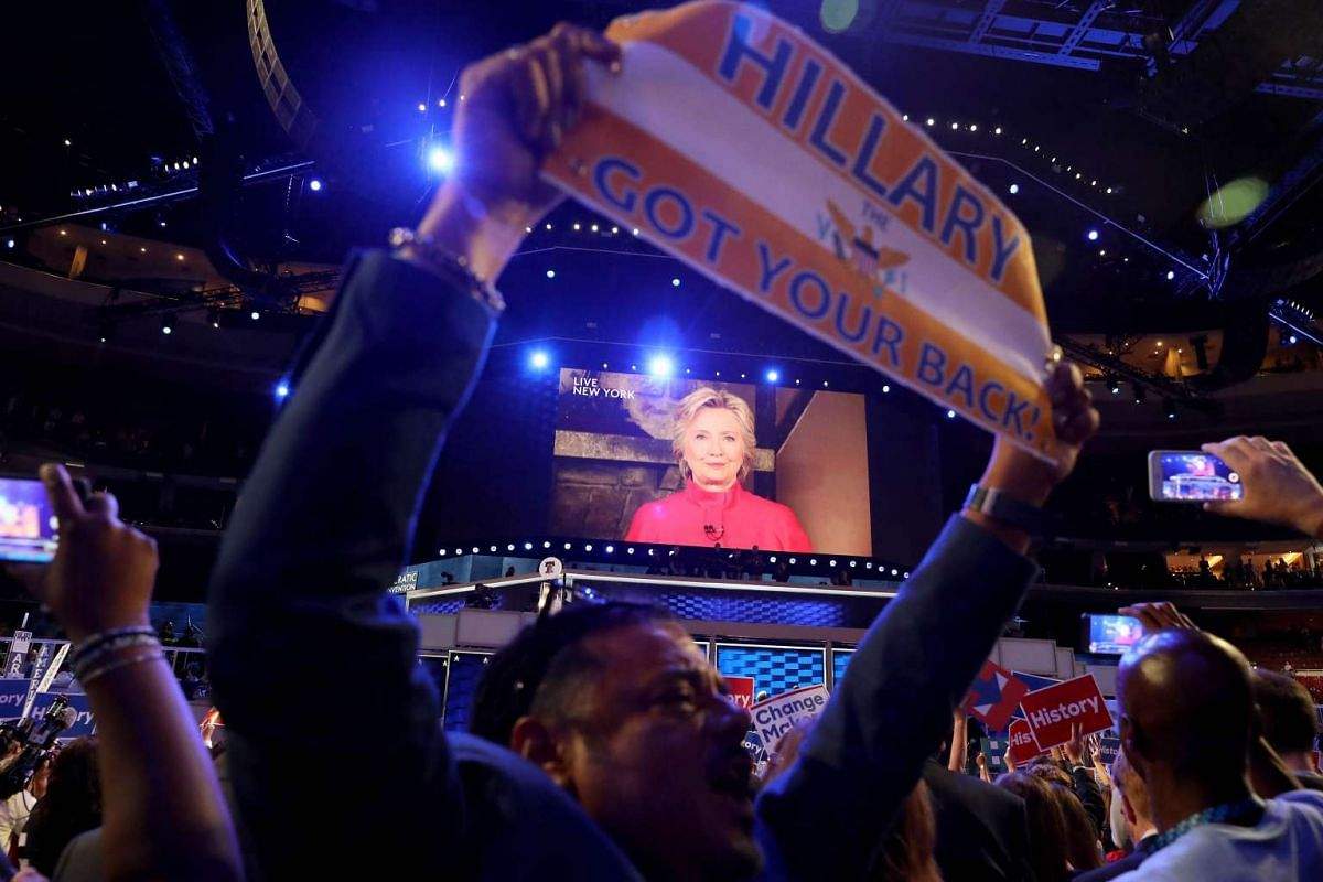 Delegates cheer as a screen displays Democratic presidential candidate Hillary Clinton delivering remarks to the crowd during the evening session on the second day of the Democratic National Convention at the Wells Fargo Center, July 26, 2016 in Phil