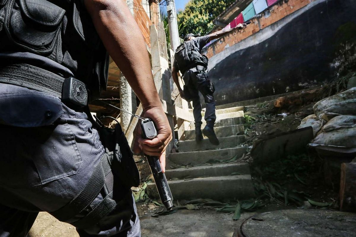 Police officers patrol in the Babilonia favela community, which stands on a hillside above Copacabana beach, an Olympic venue site, on July 26, 2016 in Rio de Janeiro, Brazil.  PHOTO: GETTY IMAGES/AFP